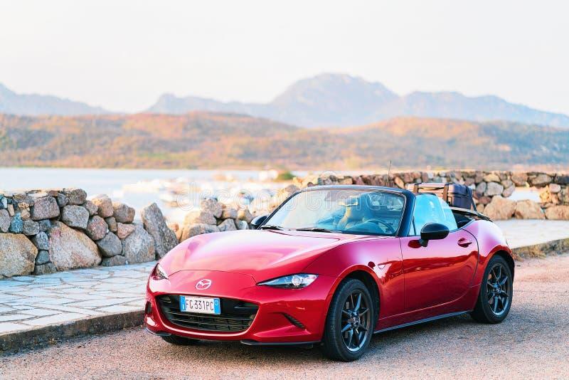 Красный автомобиль cabriolet на Косте Smeralda Сардинии дороги стоковые изображения rf