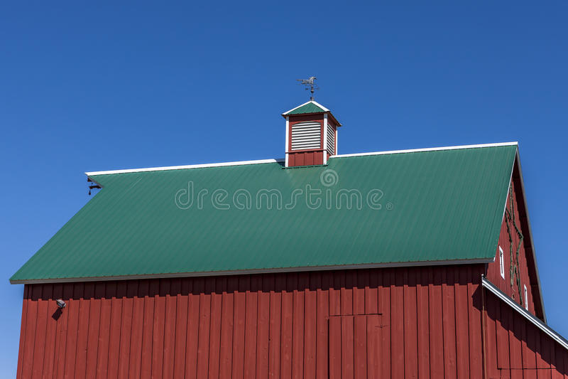 Красный амбар, зеленая крыша, голубое небо, стоковые изображения