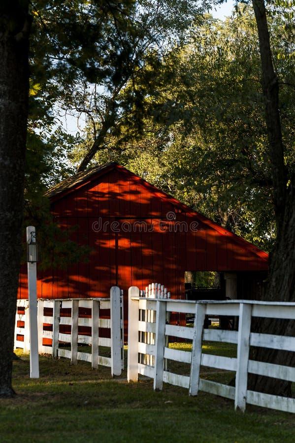 Красный амбар и белая загородка - деревня шейкера Pleasant Hill - центральный Кентукки стоковое изображение rf