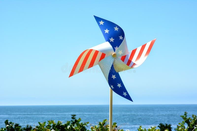 Красный белый и голубой патриотический Pinwheel с голубым небом и океаном стоковые фото