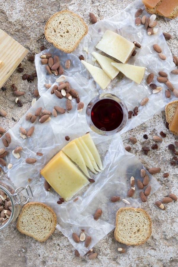 Красный бокал сопровоженный разнообразием сыров, зажаренной в духовке миндалиной стоковая фотография