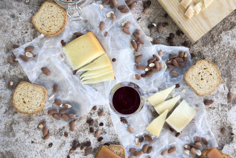 Красный бокал сопровоженный разнообразием сыров, зажаренных в духовке миндалин стоковые изображения rf