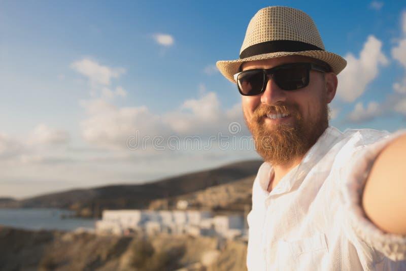 Красный бородатый путешественник битника в солнечных очках и шляпе делает selfie на каникулах на предпосылке seashore стоковые изображения rf