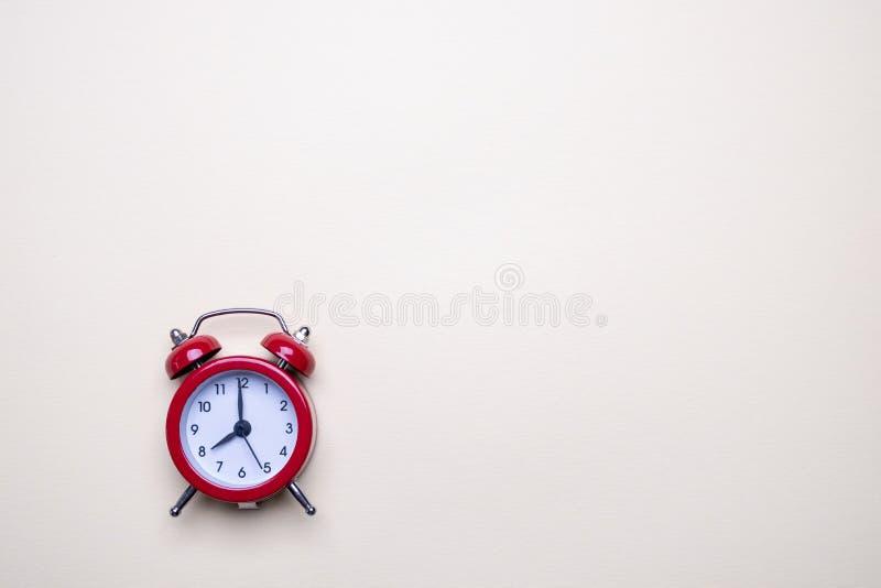 Красный будильник на светлой пастельной предпосылке Пустое примечание для текста E r Минимальный стоковое изображение rf