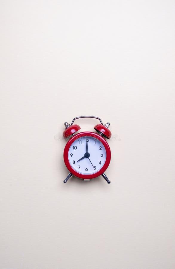 Красный будильник на светлой пастельной предпосылке Пустое примечание для текста E r Минимальный стоковая фотография rf