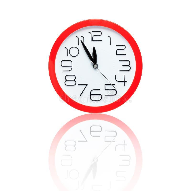 Красный будильник показывая 5 минут к полночи с отражением стоковые изображения