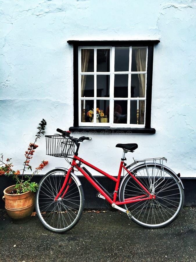 Красный велосипед под окном стоковые изображения rf