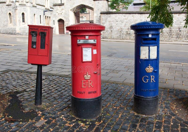Красный великобританский почтовый ящик на улице города стоковые фото