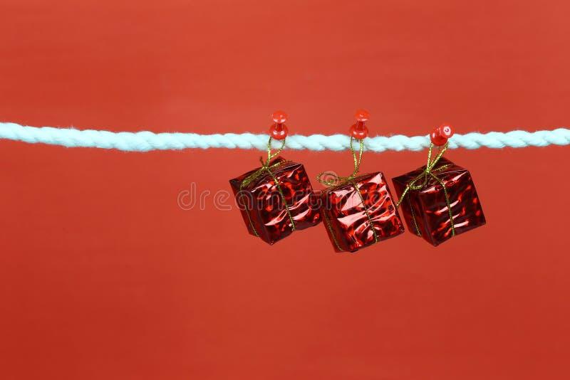 Красный вид подарочной коробки на веревке для белья и иметь космос экземпляра с красной предпосылкой стоковые изображения rf