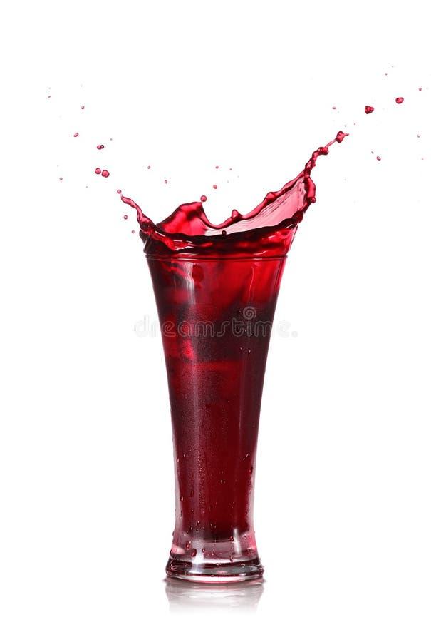 Красный выплеск сока в стекле стоковые изображения