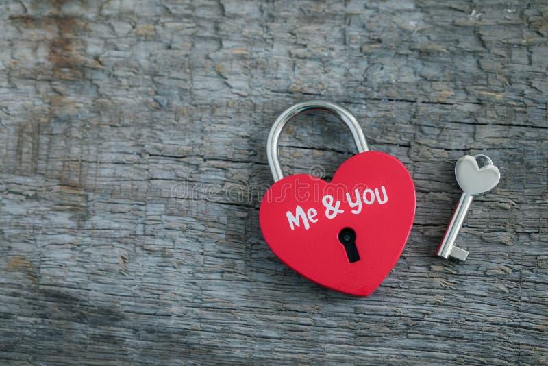 Красный в форме сердц padlock с ключом на деревянной открытке предпосылки, дня St Валентайн или замужества стоковая фотография