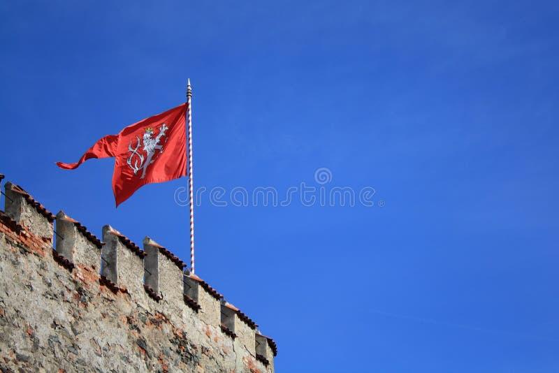 Красный герб чехии Флаг с львом на крепости на голубом небе стоковые фото