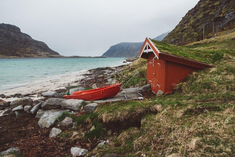 Красный деревянный дом с мхом на крыше и шлюпке на предпосылке моря и гор В расстоянии красная шлюпка стоковые изображения rf