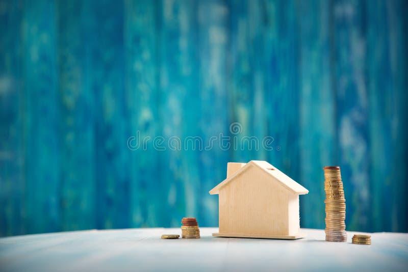 Красный дом на деревянной предпосылке с банкнотами стоковые изображения
