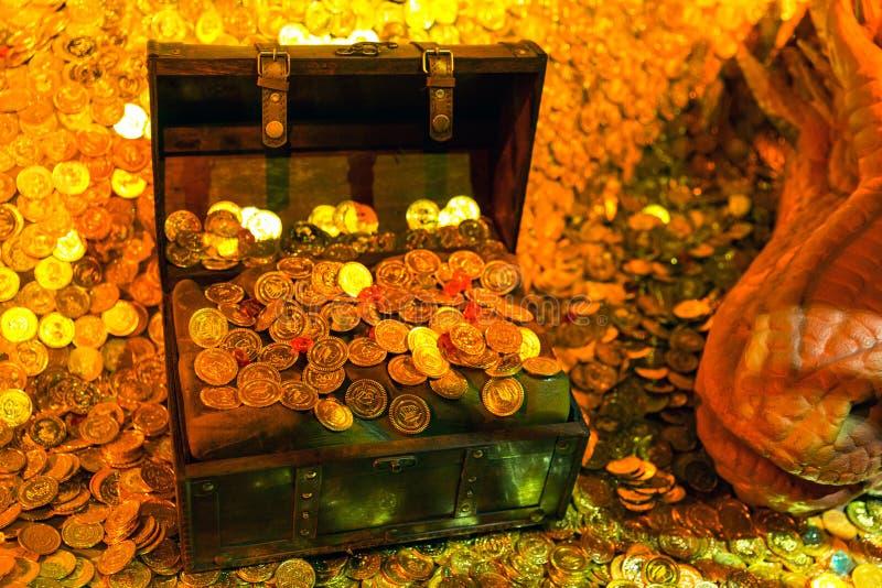 Красный дракон копя комоды сокровищ и кучи монеток стоковые фотографии rf