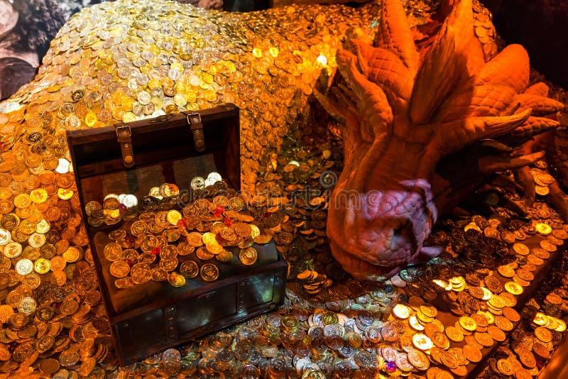 Красный дракон копя комоды сокровищ и кучи монеток стоковое изображение