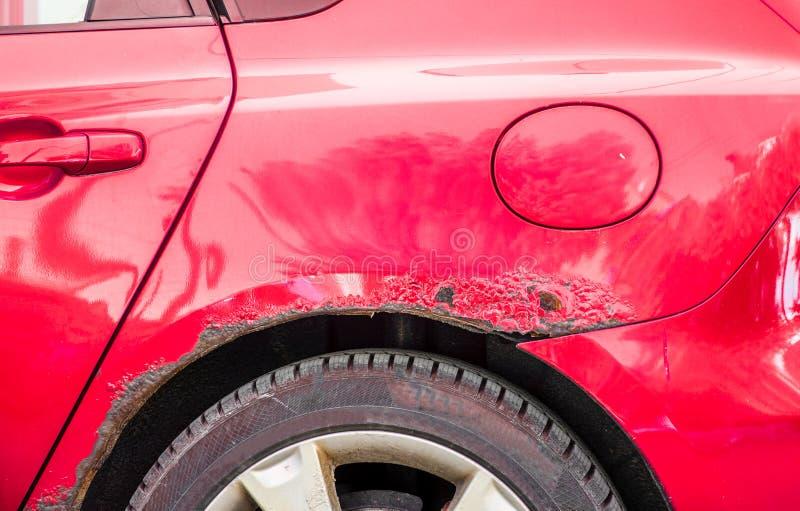 Красный заржаветый и поцарапанный автомобиль с поврежденной ржавой краской в аварии или парковке аварии стоковое изображение