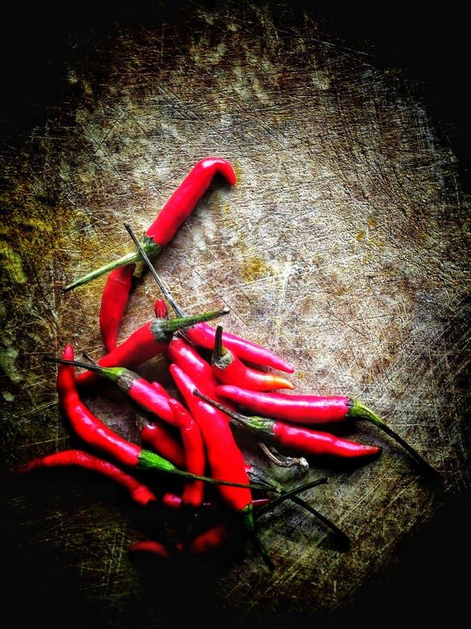 Красный затир chili на старой деревянной прерывая доске стоковое фото