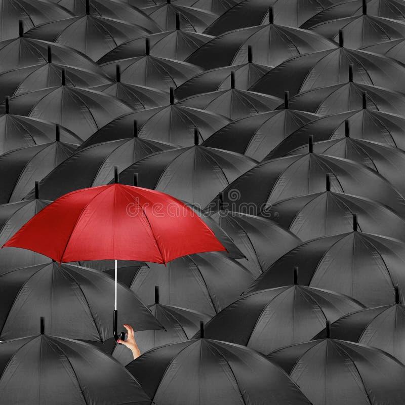 Красный зонтик посреди много черных зонтиков стоковые изображения rf