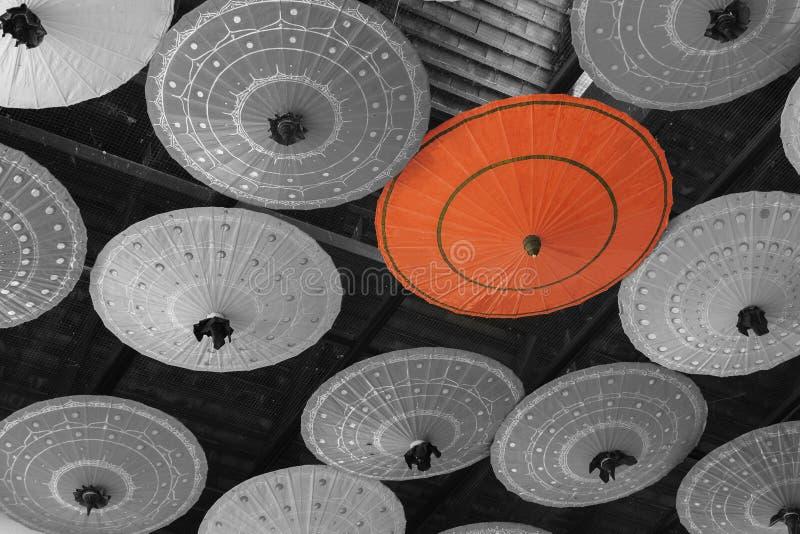Красный зонтик стоит вне от толпы много черно-белого um стоковые изображения rf