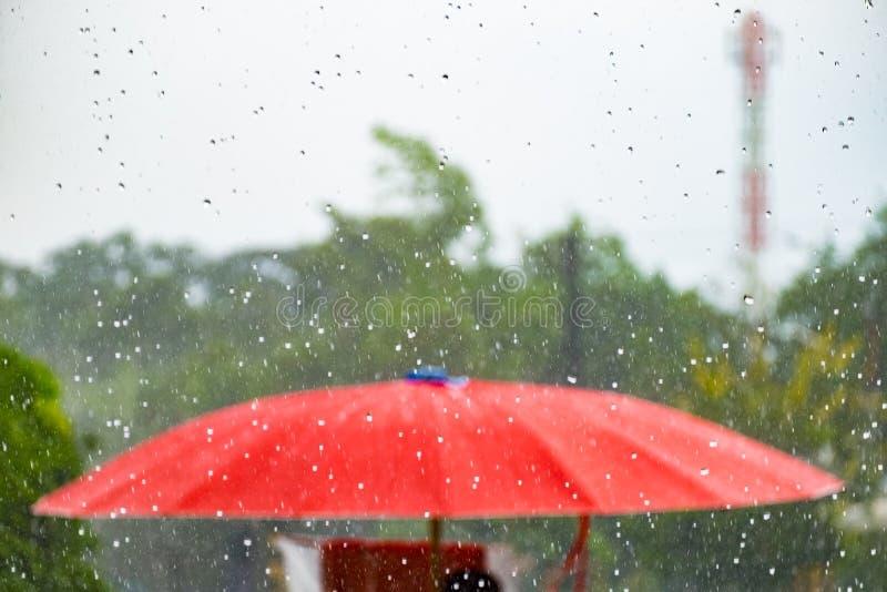 Красный зонтик с дождем падения шторма стоковое фото rf