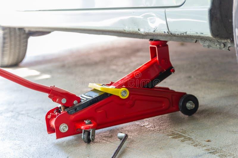 Красный инструмент поднимает автомобиль домкратом подъема для обслуживания проверки ремонта стоковые фото