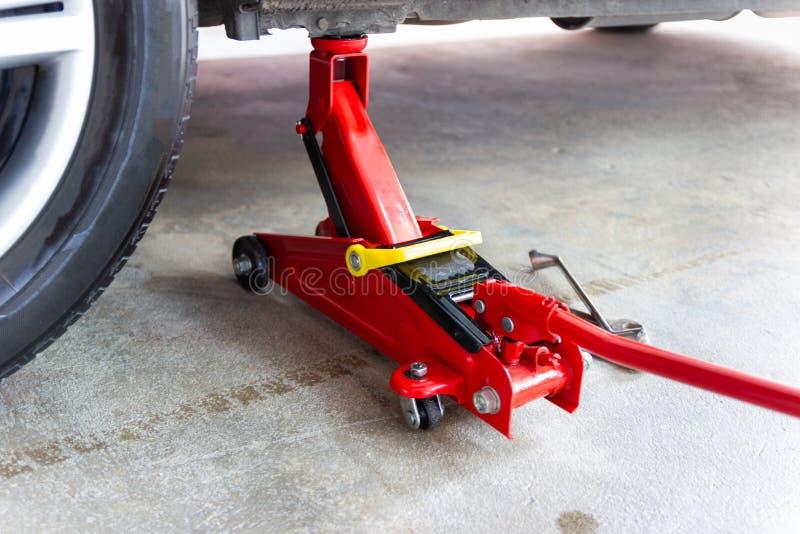Красный инструмент поднимает автомобиль домкратом подъема для обслуживания проверки ремонта стоковые фотографии rf