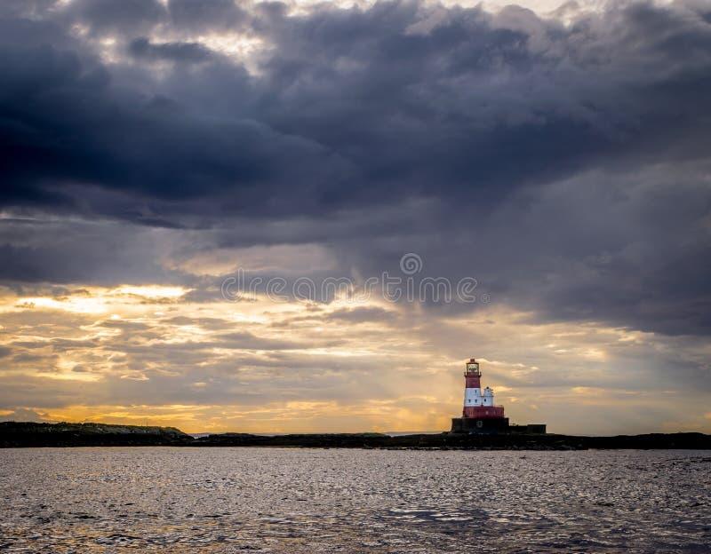 Красный и белый маяк на острове окруженном облаками шторма стоковая фотография