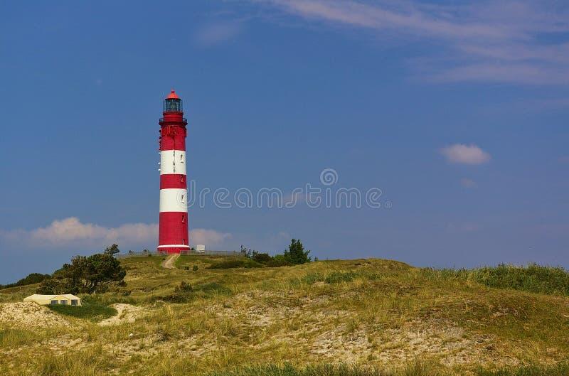 Красный и белый маяк на песчанной дюне слегка покрытой с травой пляжа перед голубым небом стоковая фотография