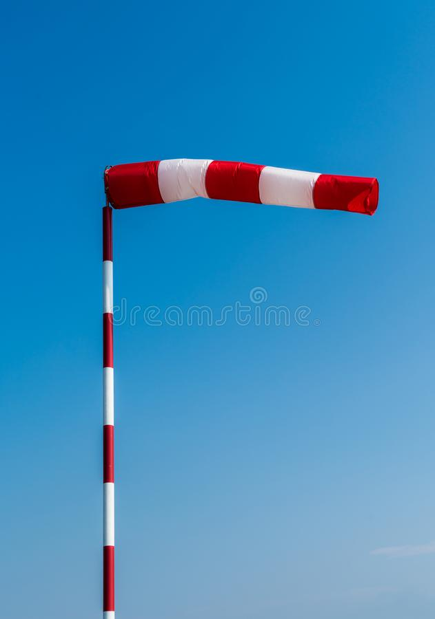 Красный и белый Windsock на поляке с трудным ветром стоковое фото rf