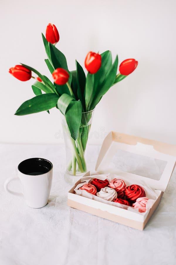 Красный и белый zephyr с чашкой чаю и красными тюльпанами на белой предпосылке стоковые изображения rf