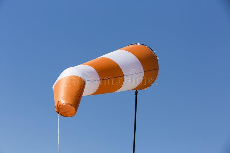 Красный и белый ветер windsock заполнил предпосылку голубого неба стоковое фото rf