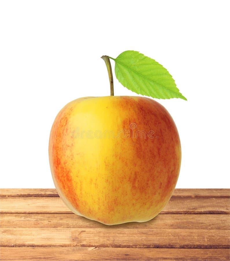 Красный и желтый плодоовощ яблока с зелеными лист на isola деревянного стола стоковая фотография