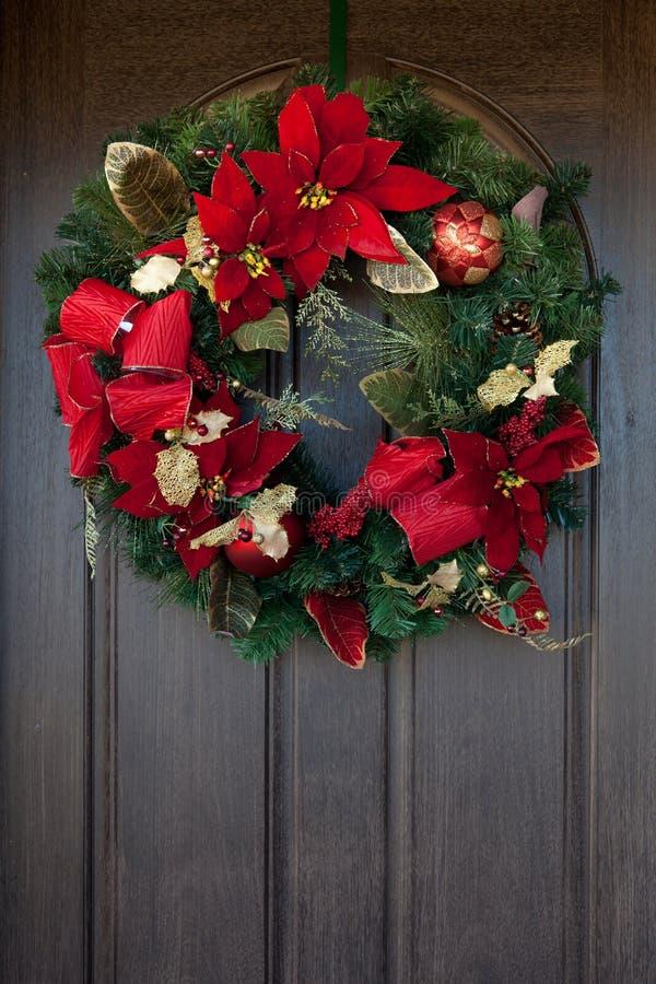 Красный венок Кристмас на деревянной двери стоковая фотография