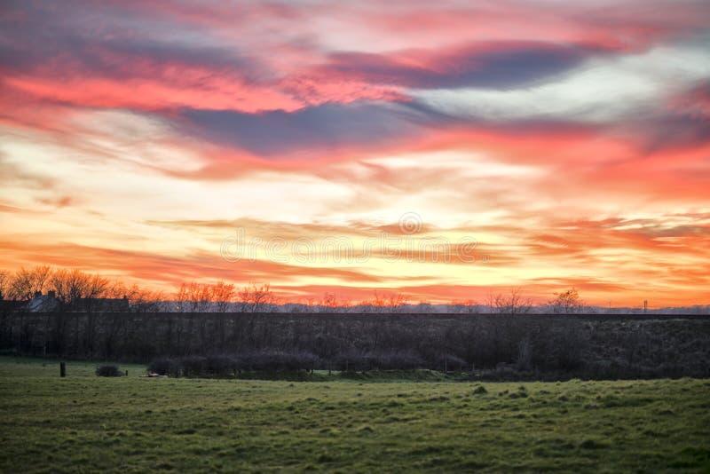 Красный и фиолетовый ландшафт захода солнца неба стоковая фотография rf