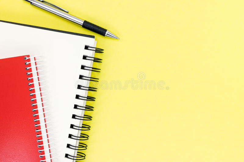 Красный и черный блокнот с открытой чистой страницей и ручка на желтой плате стоковое фото