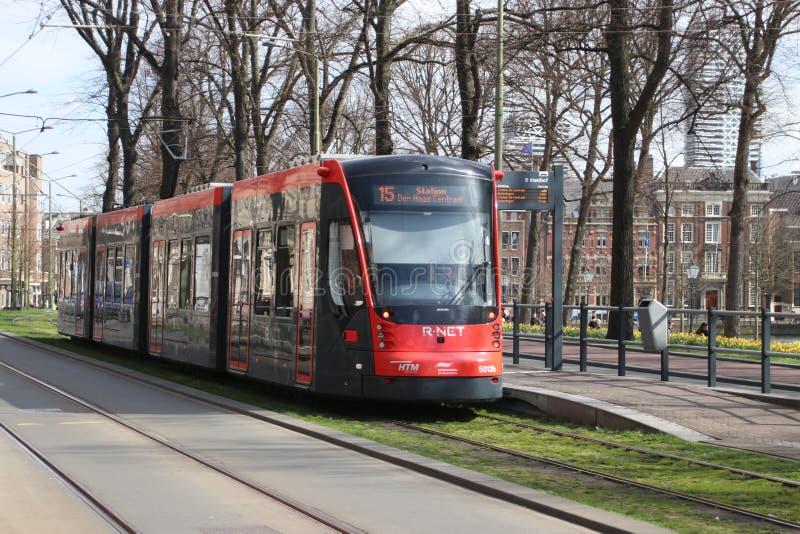 Красный и черный покрашенный автомобиль улицы трамвая Avenio Сименс в вертепе Haag Гааги в Нидерланд стоковое фото rf