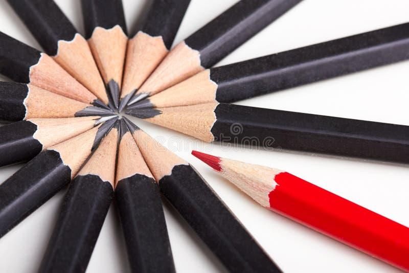 Красный карандаш стоя вне от толпы стоковое фото rf