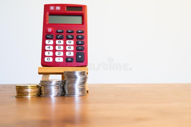 Красный карманный калькулятор на мольберте с стогами монеток стоковое изображение rf
