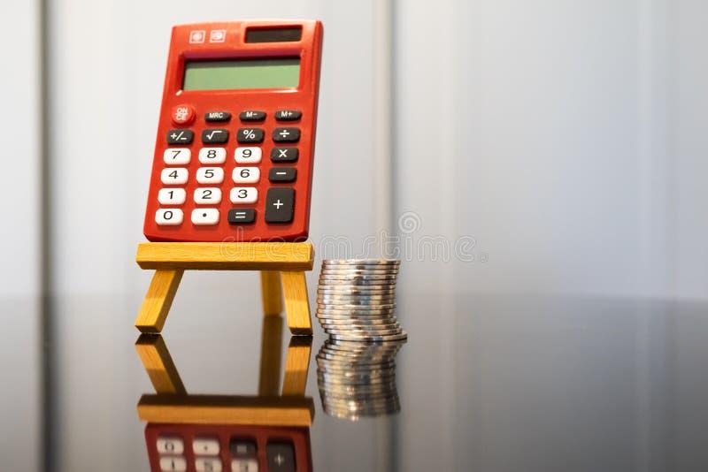 Красный карманный калькулятор на мольберте с стогом монеток стоковая фотография