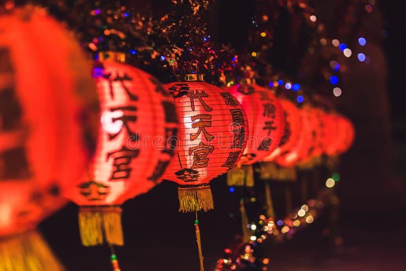 Красный китайский текст иероглифа lanternTranslation С Новым Годом! вися в ряд во время времени дня для китайского торжества Ново стоковые фотографии rf