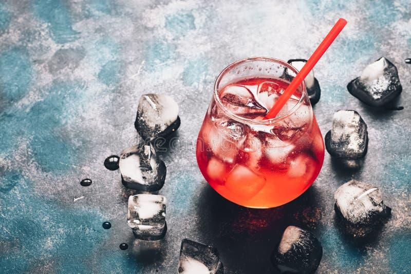 Красный коктеиль с льдом на черной голубой поверхности Яркое, красное питье в backlight скопируйте космос стоковая фотография