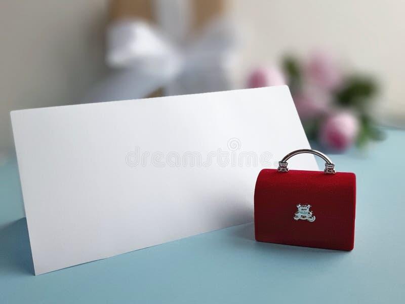 Красный комод ювелирных изделий бархата с пустой сложенной картой на голубой предпосылке Концепция праздника свадьбы стоковые изображения
