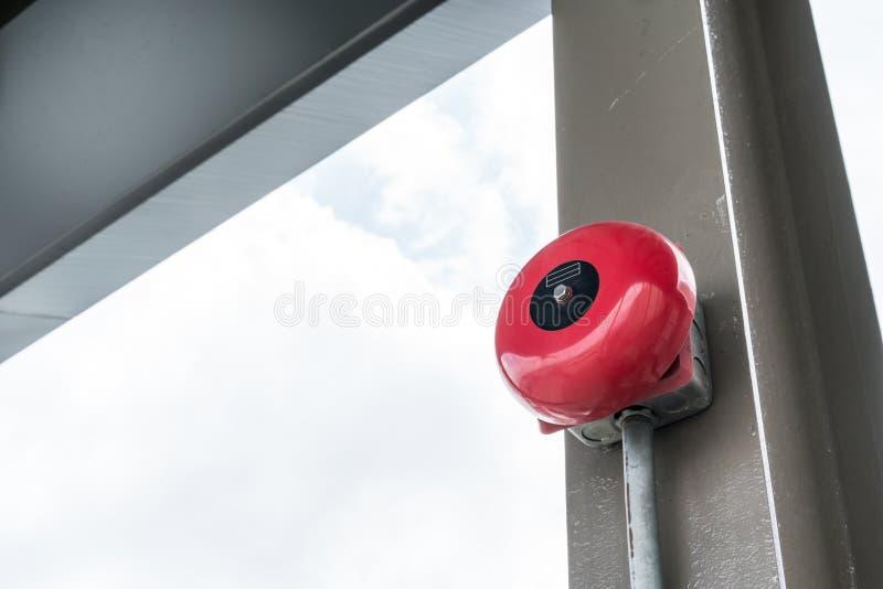 Красный колокол пожарной сигнализации на рамке металла стоковое фото