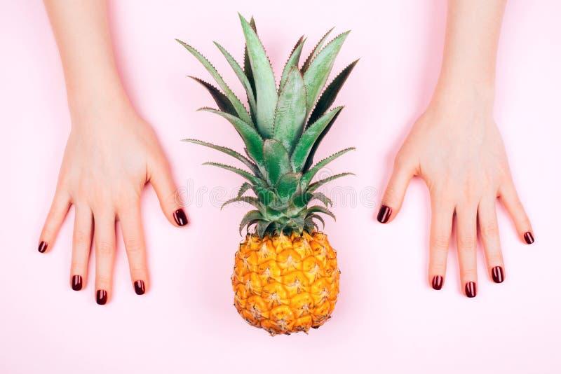 Красный маникюр на розовой предпосылке с ананасом стоковое фото