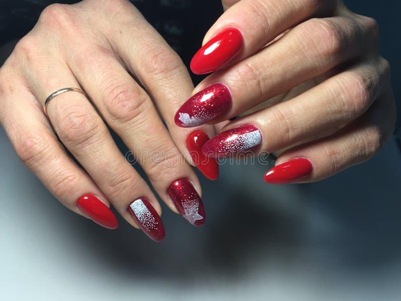 красный маникюр с белыми снежинками на длинных ногтях стоковое изображение rf