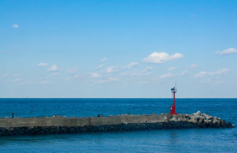 Красный маяк морем стоковое изображение