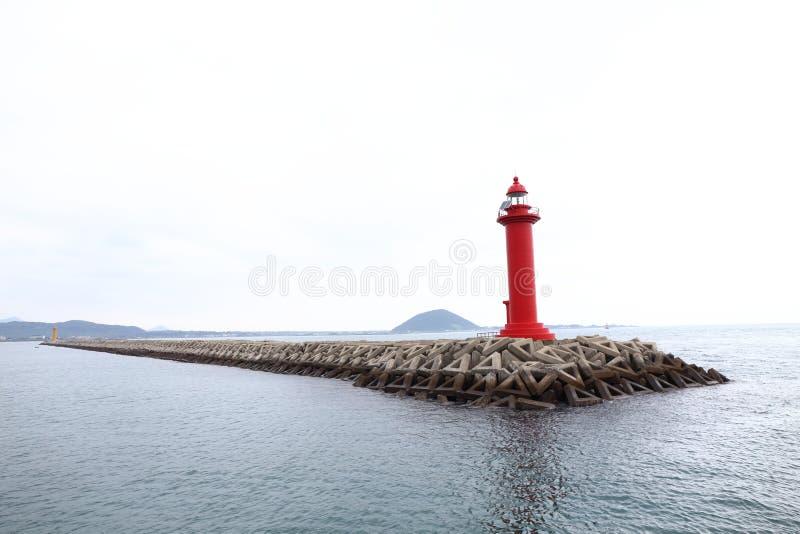 Красный Красный маяк острова Удо в Чеджу, Корея, остров Удо был назван потому, что он напоминает лживую корову стоковая фотография