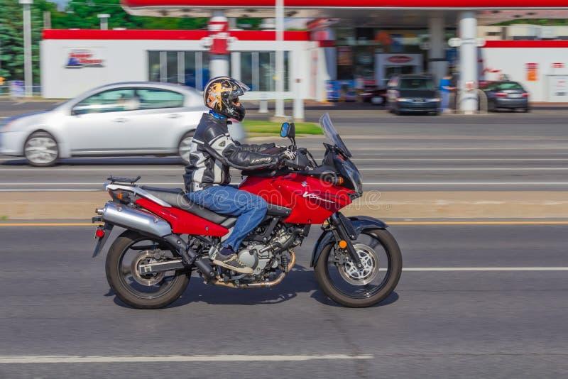 Красный мотоцикл управляя на быстром ходе стоковое фото