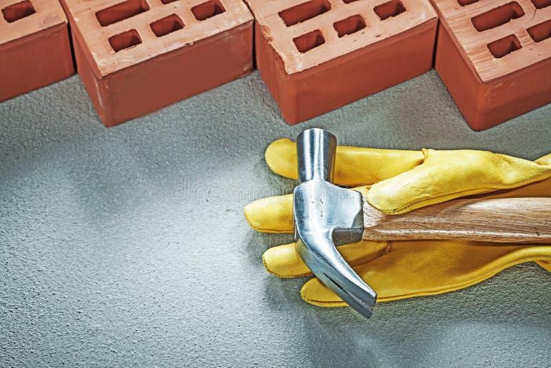 Красный молоток с раздвоенным хвостом защитных перчаток кирпичей конструкции на concret стоковые фото